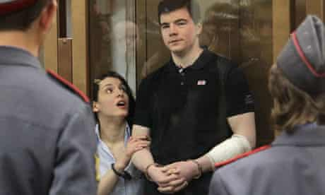 Yevgenia Khasis and Nikita Tikhonov stand in a glass cell at the Moscow City Court