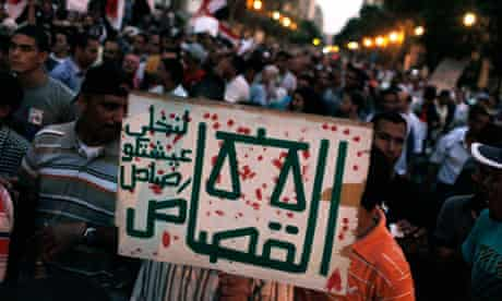 """A protester in Tahrir Square carries a placard that reads """"Justice or bullets"""" in Arabic."""