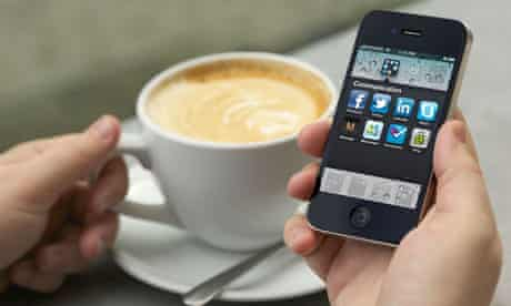 Man hand holding an iPhone 4 showing the social networking application screen at a cafe