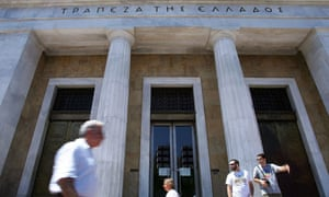 People walk past the headquarters of the Bank of Greece in central Athens