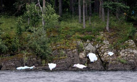 Covered corpses are seen on the shore of the small, wooded island of Utoeya