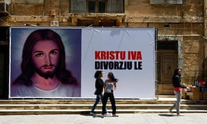 "Young women walk past a billboard reading ""Christ Yes, Divorce No"" in Sliema"