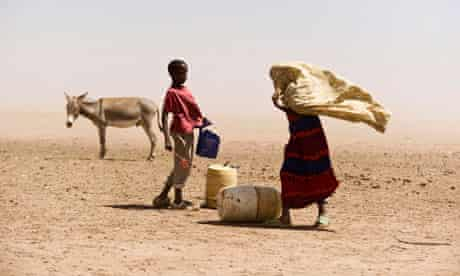 People and a donkey stand near water containers in Wajir