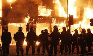 Riot police near burning building in Tottenham