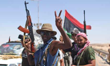 A rebel fighter flashes a victory sign at the gates of the town of Brega, Libya