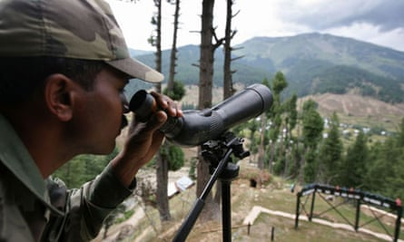 An Indian soldier looks out across the line of control dividing Kashmir.
