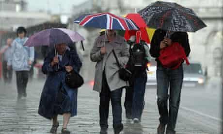 People walk with umbrellas in heavy rain