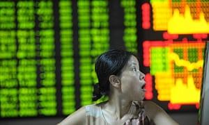 An investor watches an index screen at a stocks brokerage house in Hefei, China.