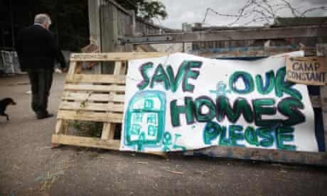 A traveller walks past a 'save our homes' sign erected at the gates of Dale Farm