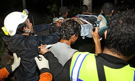 Rescuers carry a survivor of the helicopter crash in Indonesia, but he later died from his injuries.