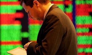 A trader watches the market prices at the stock exchange in Sydney.