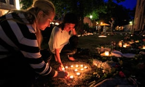 Youths light candles among flowers and tributes outside the Oslo Cathedral