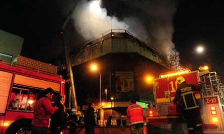 Firefighters battle a blaze in a store in Santiago