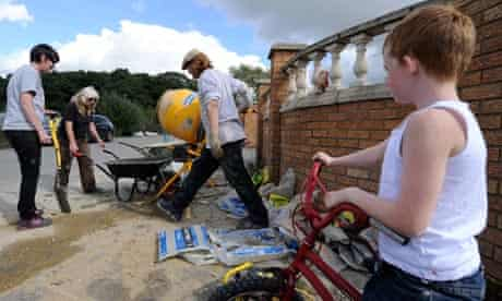 Men mix cement to construct a brick wall to block bailffs