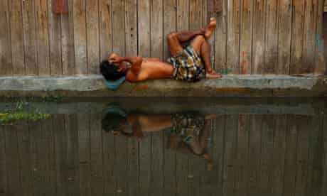 A worker takes a nap during sea water tidal flooding in Semarang, Indonesia