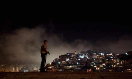 A policeman patrols a slum district of Caracas