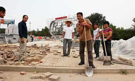 Migrant workers spray paint on a steel map monument in Daxing, southern Beijing