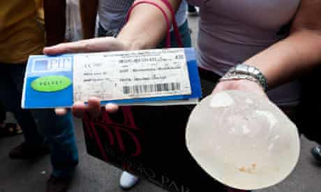 Woman holds her defective PIP breast implant