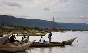 Fishermen row next to an oil exploration site in Uganda