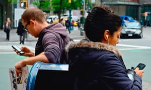 Two people leaning on mail box while using iPhones near Columbus Circle, New York City
