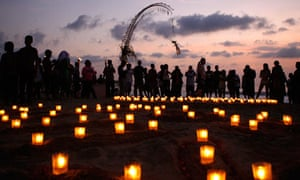 Relatives and survivors light candles at the beach during a memorial ceremony in Kuta, Bali