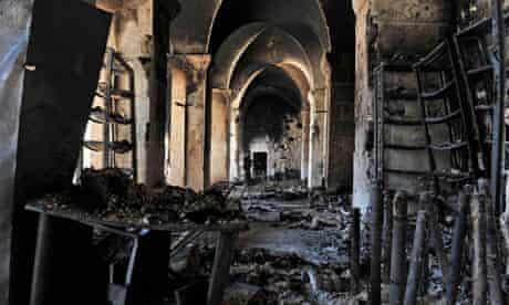 A Syrian rebel (rear) walks inside a bur