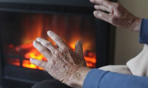 Man warms hands in front of fire