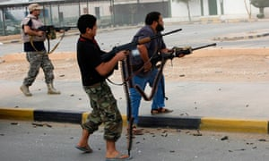 Libyan militiamen shoot at a building in Bani Walid