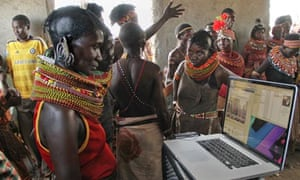 Turkana women examine photos of a festival rehearsal on a laptop in Loiyangaleni, Kenya.