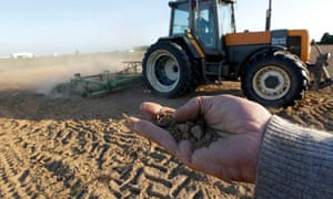 A farmer holds dry earth in his hand as a tractor is operated in a field in Blecourt