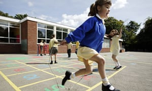 Schoolgirls skip in primary school playground