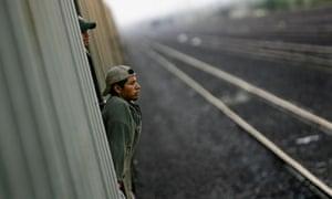 Immigrants travel on a cargo train to the border city of Nuevo Laredo, Mexico