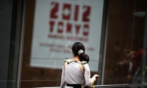 A woman walks by the venue of the annual IMF meeting, in Tokyo.