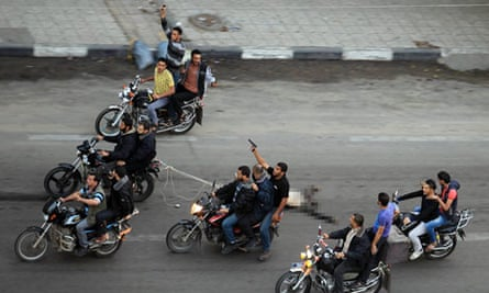Gunmen on motorcycles drag the body of a man executed by Hamas's military wing