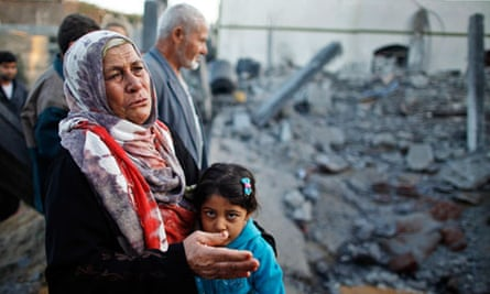 A Palestinian woman cries next to a house destroyed in an Israeli air strike in Beit Lahiya