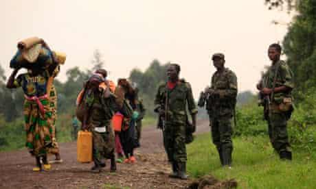 families walk past M23 rebels at Rumangabo