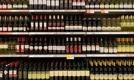 Bottles of cheap red wine on shelves in a budget supermarket in the UK