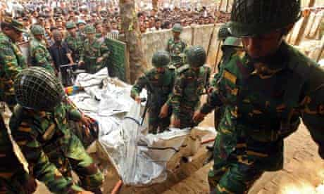 Soldiers help carry the bodies of workers killed in the fire at a garment factory in Dhaka.