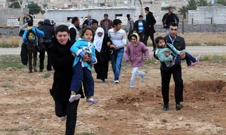 Syrians flee from the Rasulayn region across the border into the Turkish town of Ceylanpinar.