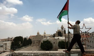 A Palestinian man fixes a national flag in Bethlehem