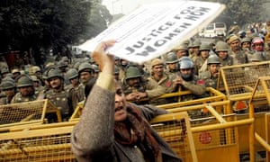 An Indian woman climbs on a police barricade during a protest for women's rights, in New Delhi.