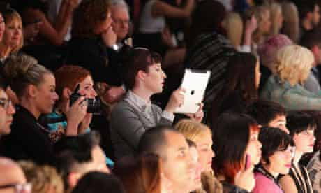 An audience member photographs with an iPad at the Toi Et Moi fashion show in Sydney