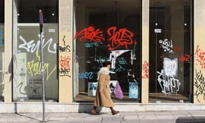 A woman walks past a closed-down shop in Athens