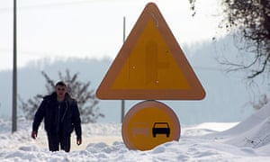 A man walks through a road covered with snow in Uzice, Serbia.