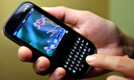 Man holds a Palm Pixi smartphone from Sprint
