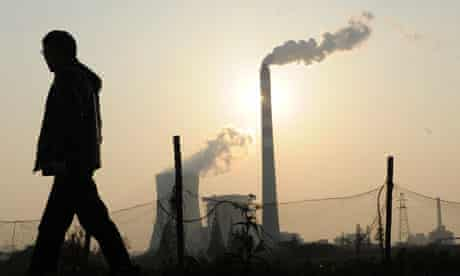 A man walks past as smoke billows from chimneys at a power station in Hefei, Anhui, China
