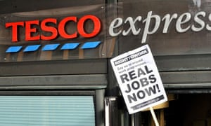 A Right to Work campaigner holds a banner outside the Tesco Express at Westminster