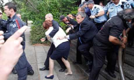 Bodyguards hustle Prime Minister Julia Gillard away during an Aboriginal protest