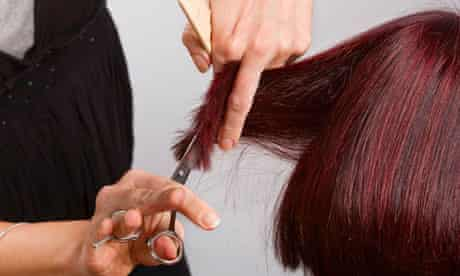 Hairdresser at work cutting customers hair