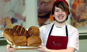 Young man holding loaves of bread